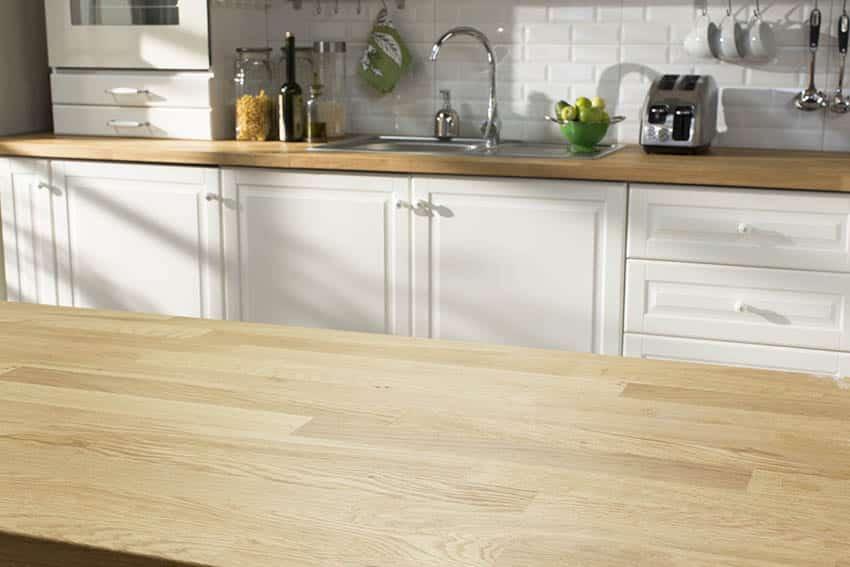 White kitchen with light wood kitchen countertops tile backsplash