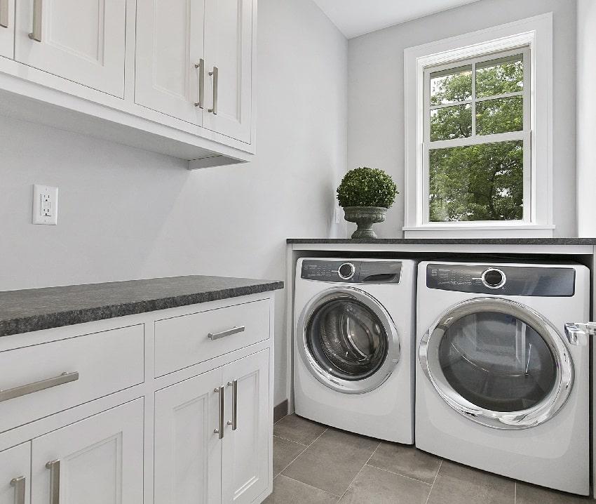 lavadero blanco con secadora de ropa y gabinetes blancos