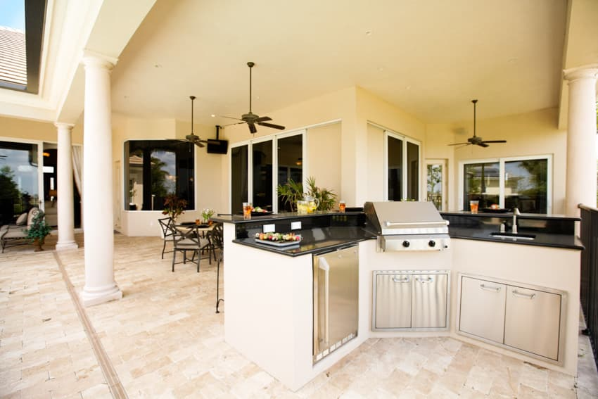 White outdoor kitchen with sink grill countertop dining table and chairs
