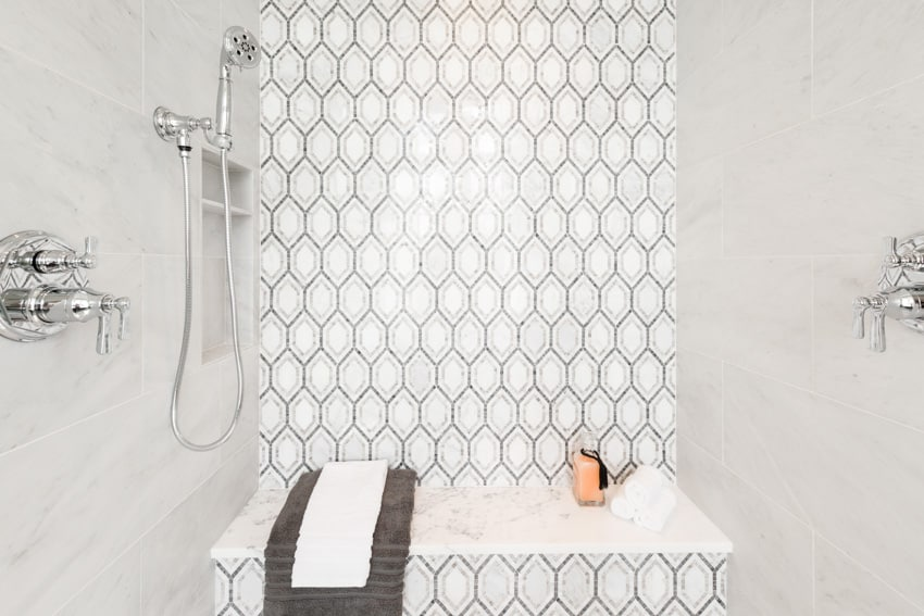 White room with shower bench and patterned wall