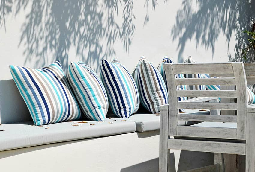 Whitewash outdoor chair next to cushioned bench seat