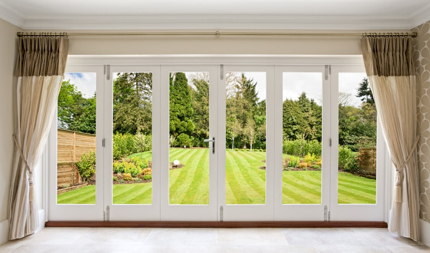 Wide folding patio door with curtains leading to backyard