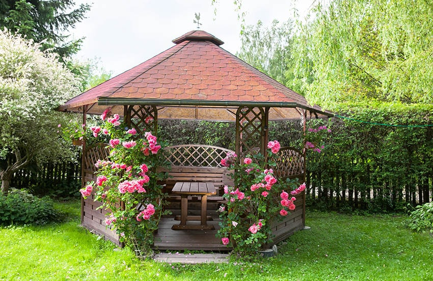 Wood gazebo with pink roses wood table bench
