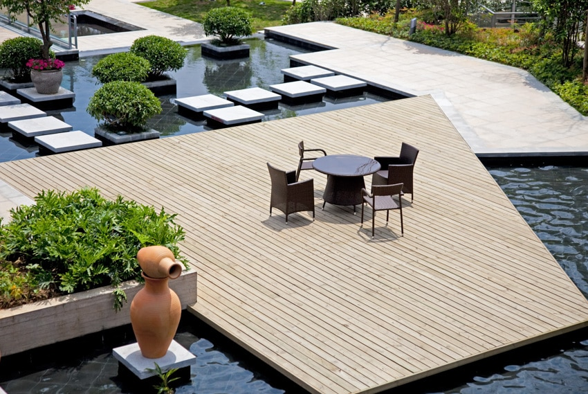 Wooden deck in the middle of pool with table and chairs on it