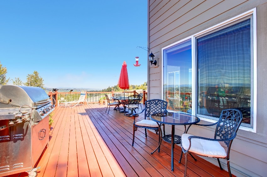wooden walkout ipe deck with patio table and barbecue overlooking beautiful landscape