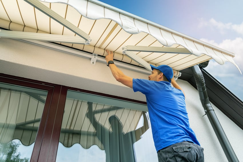 Worker installing an awning on the house wall