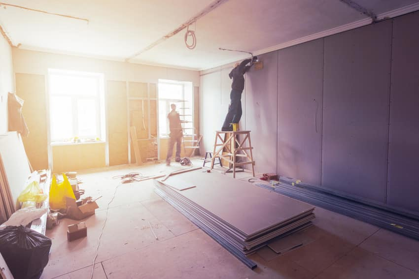 Workers installing plasterboard for gypsum walls in apartment