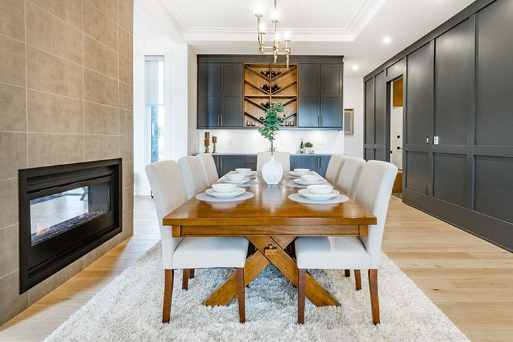 Dining room with wooden dining table black cabinets black oven is