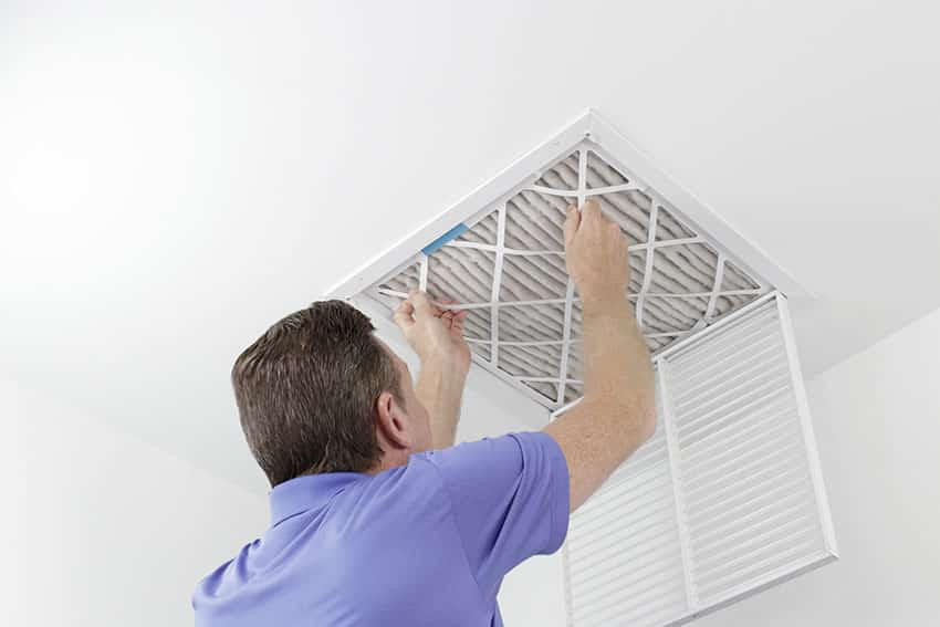 Guy removing air duct grill and filter