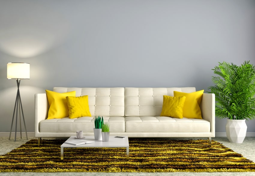 Iliving room interior with white sofa plant floor lamp coffee table and a golden carpet