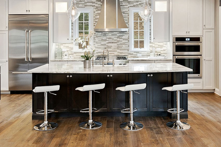 Kitchen with counter stools stainless refrigerator and stainless vent hood black cabinet