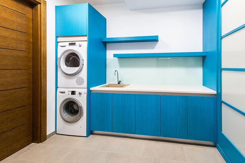 Laundry room with stacked washers blue cabinets is