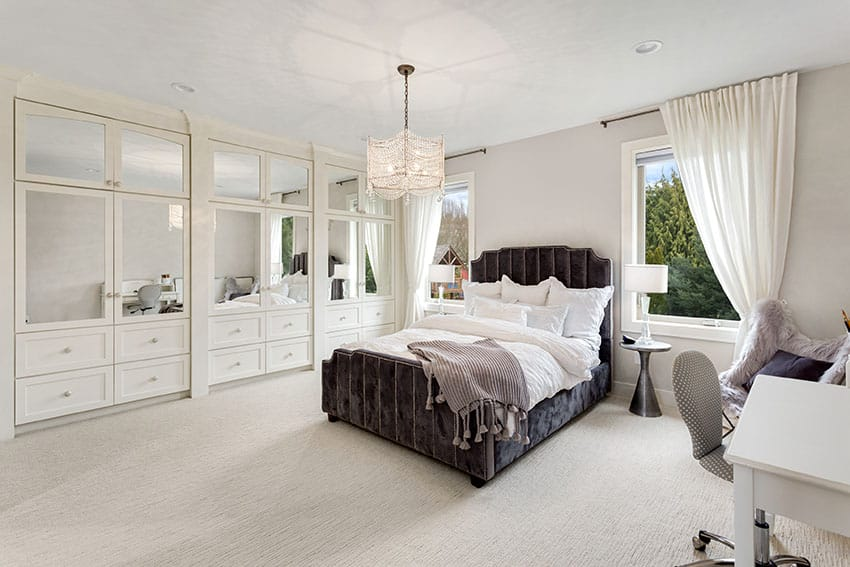 Master bedroom with built in wardrobe cabinets with drawers pendant light