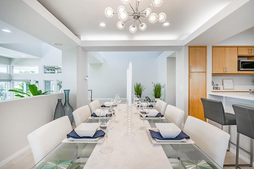 Modern dining area with glass table chandelier is