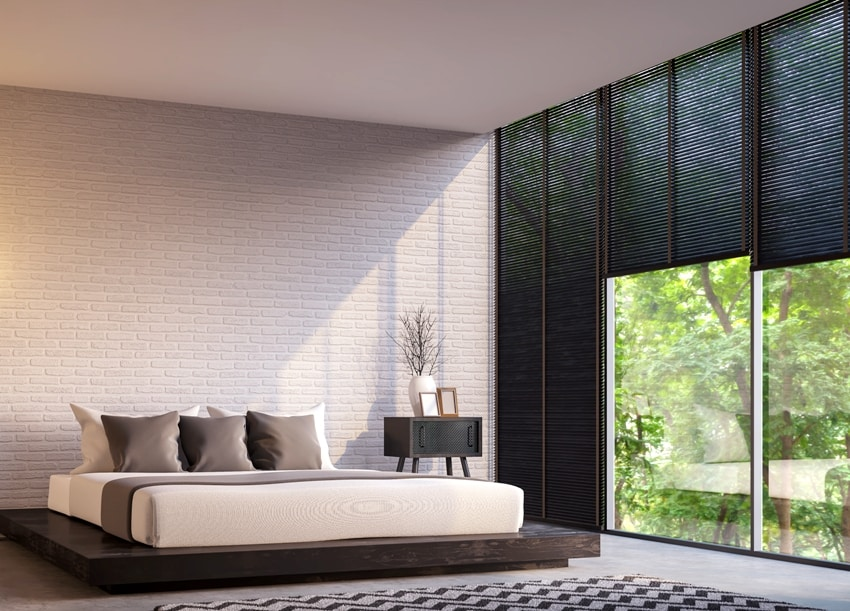 modern loft bedroom with nature view Furnished with Black wood furniture has concrete floor white brick walls large windows and blackout shades