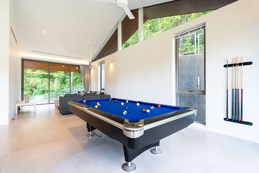 Game room with pool table white paint glass windows ceiling fans