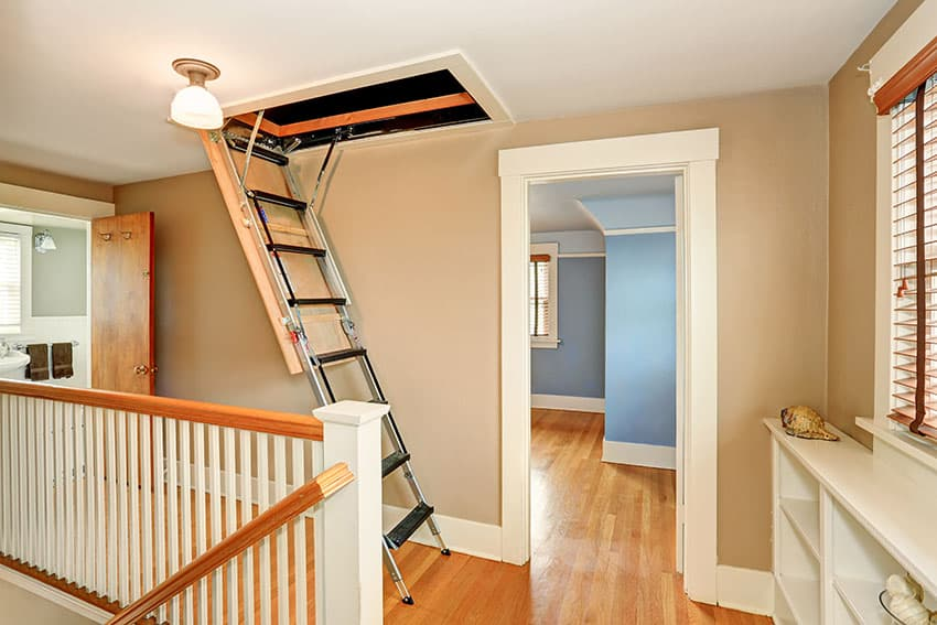 Staircase landing with ladder to scuttle attic beige paint blue room