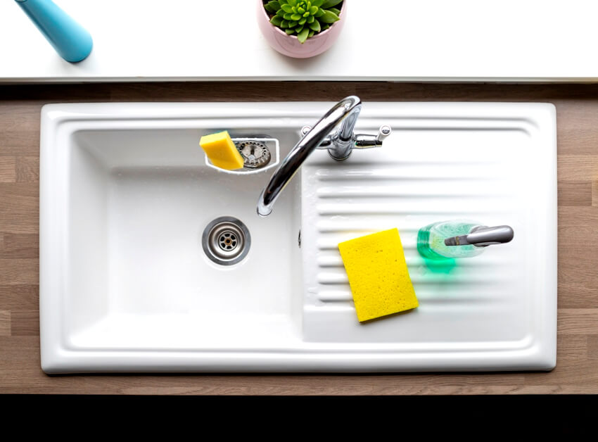 A clean kitchen cast iron sink a sponge and washing up liquid can be seen near by