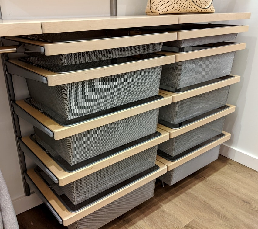 A set of wire mesh drawers inside a large walk in closet