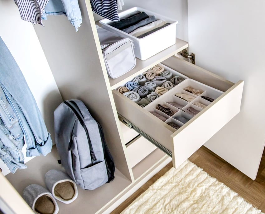 A very well organized wardrobe with clothes rolled and placed in boxes separately