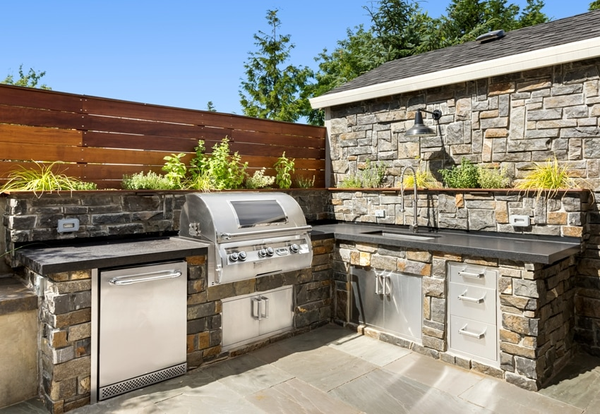 Backyard hardscape patio with outdoor barbecue and kitchen