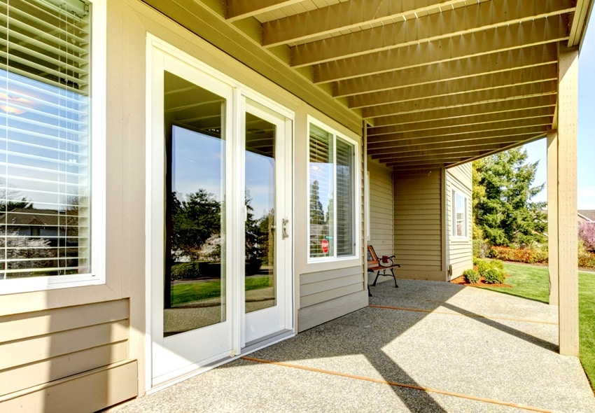 backyard walkout deck with concrete floor with a view of slide doors and windows