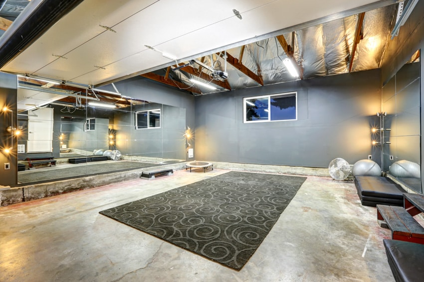 Basement with poured concrete wall mirrors and carpet