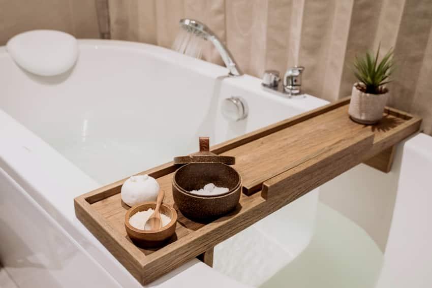 bath tub with wooden table and toiletries salt herb bath bomb in a modern bathroom