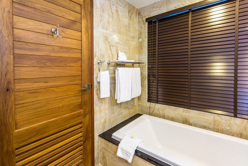 Bathroom interior with bathtub and wooden blinds