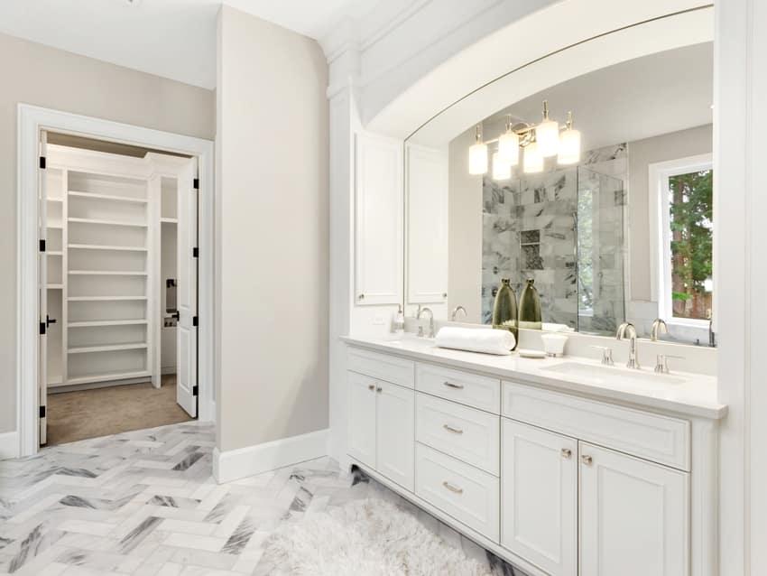 bathroom interior with beautiful circular mirror and hardwood vanity