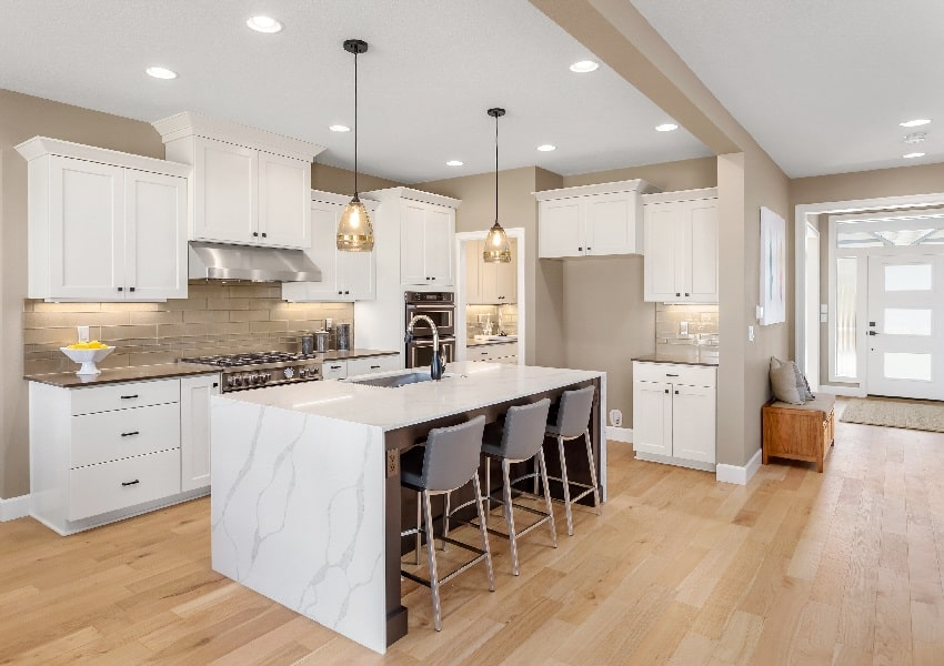 beautiful kitchen with island pendant lights and wood laminated floors
