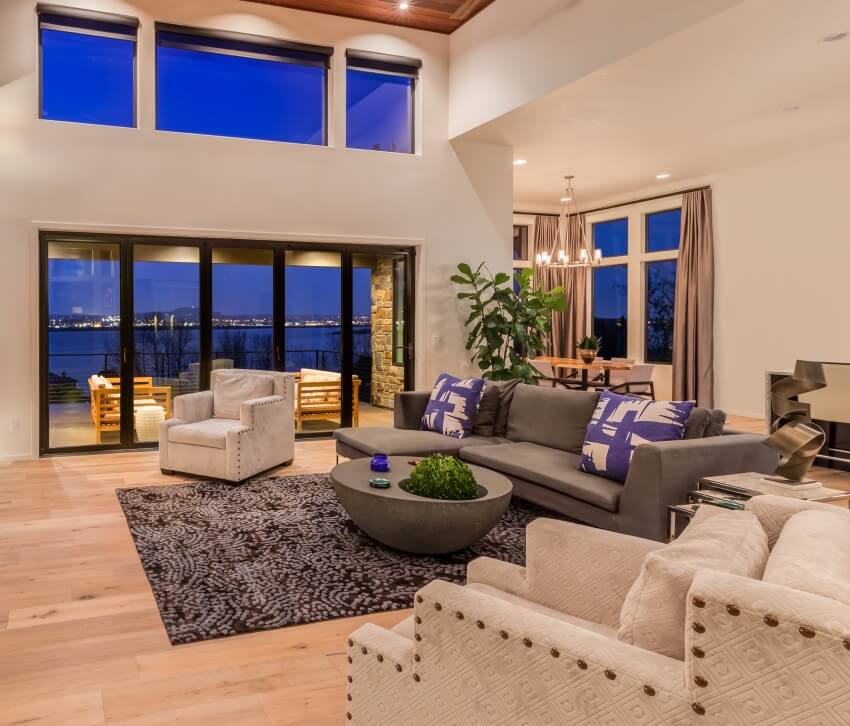 Beautiful living room in luxury home with hardwood floors and amazing view of water and city lights at night