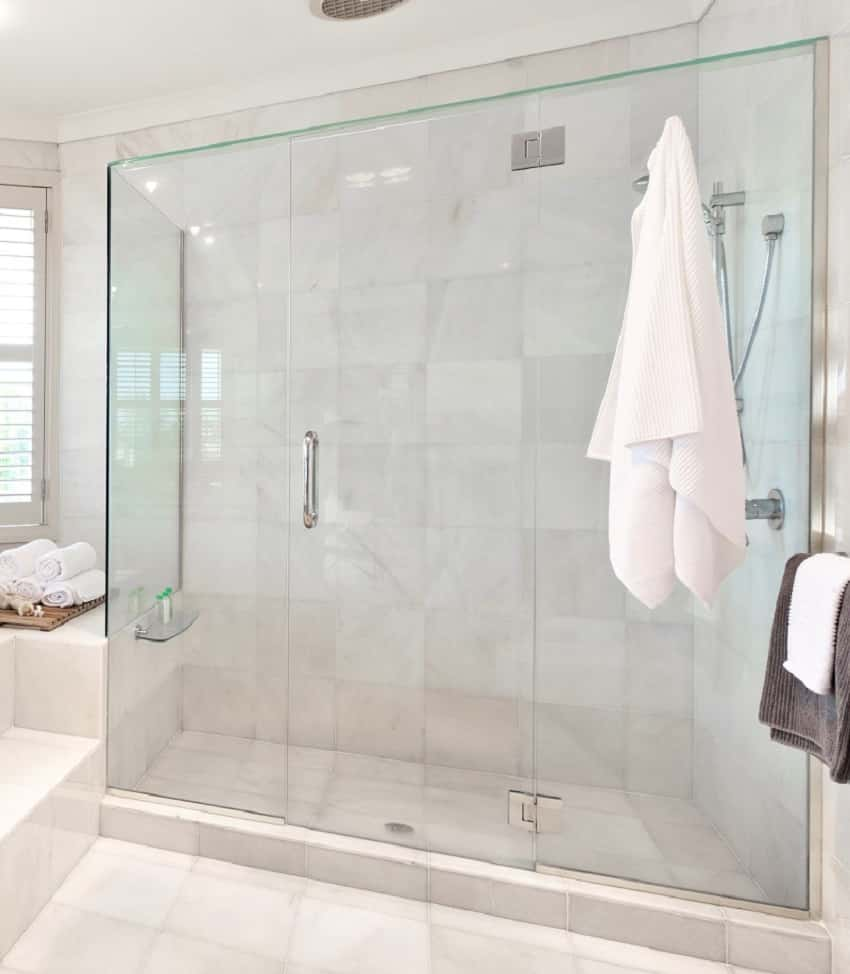 Beautiful modern bathroom with marble tiles and glass shower door