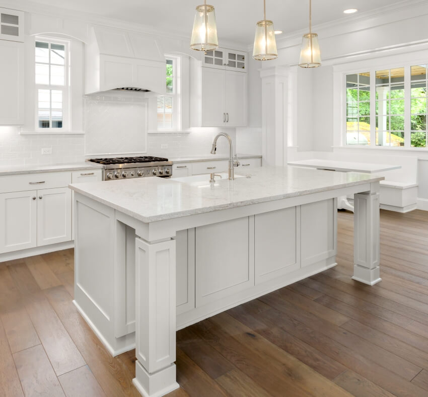 Beautiful white kitchen with white island pendant lights and hardwood floors
