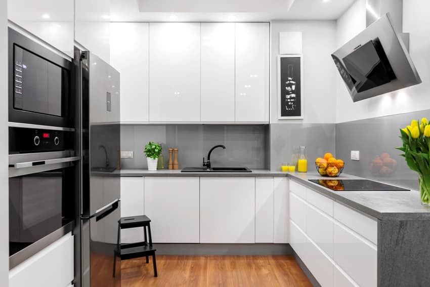 Beautifully designed kitchen in white and grey with steel elements and pvc cabinets