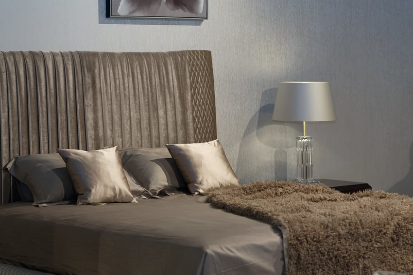 Bed with grey silk sheets decorative pillows