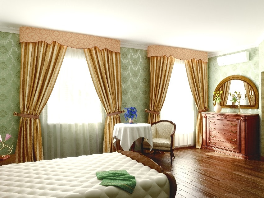 bedroom interior with gold tie up curtains green wall hardwood floors bed and wood cabinet