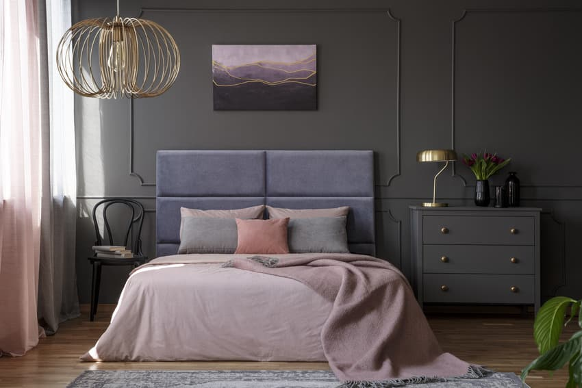 Bedroom interior with stylish light fixture poster frame and wooden flooring