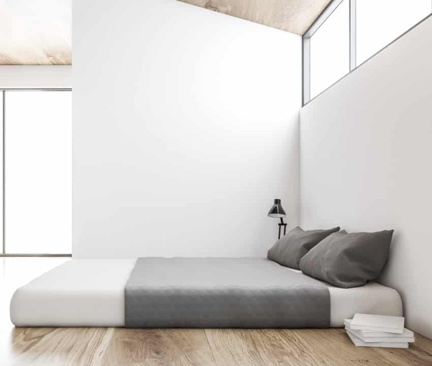 bedroom interior with white walls a king size mattress on wooden floor and a loft window