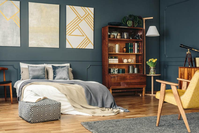 Bedroom with blue and gold elements wood shelf and carpet