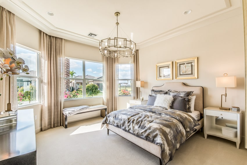 Bedroom with chandelier big windows and gold elements