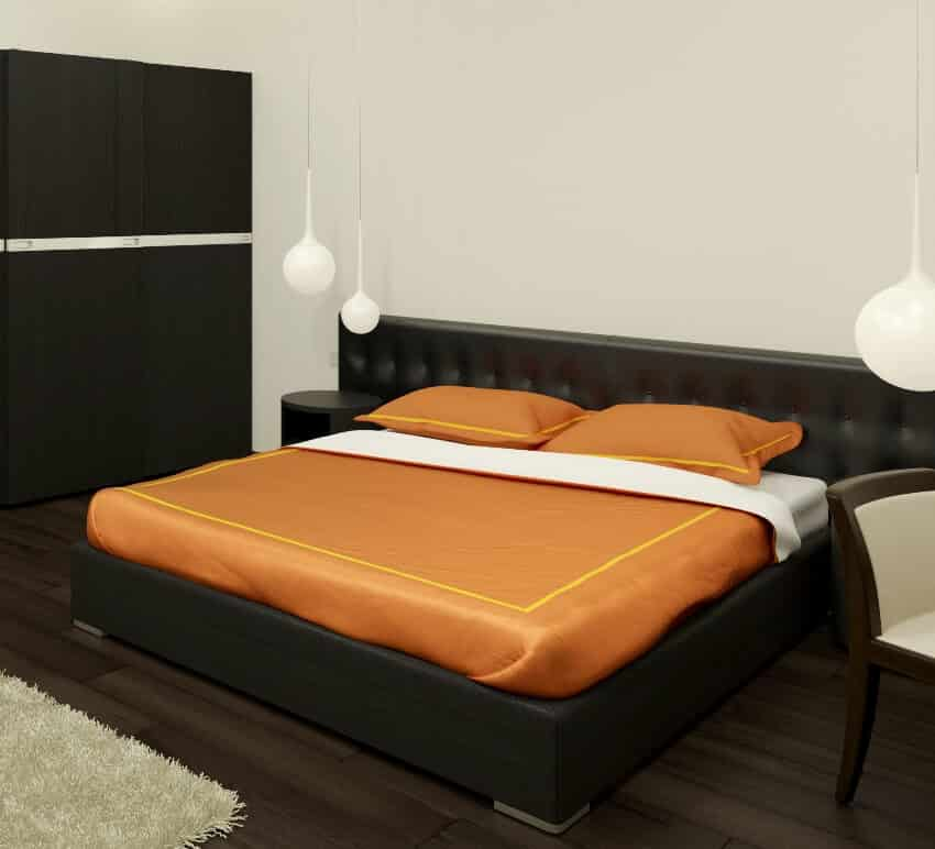 Bedroom with dark wood floors bed frame and cabinets and a bed with orange pillows and blanket