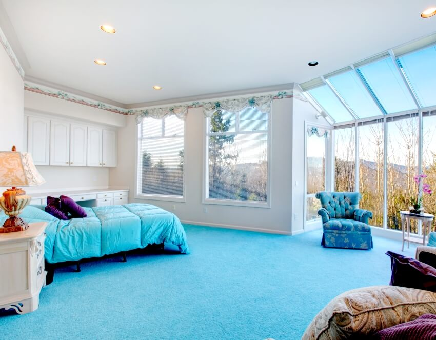 A bedroom with glass wall blue carpet floor well matched with light blue bedding and white wood storage cabinets