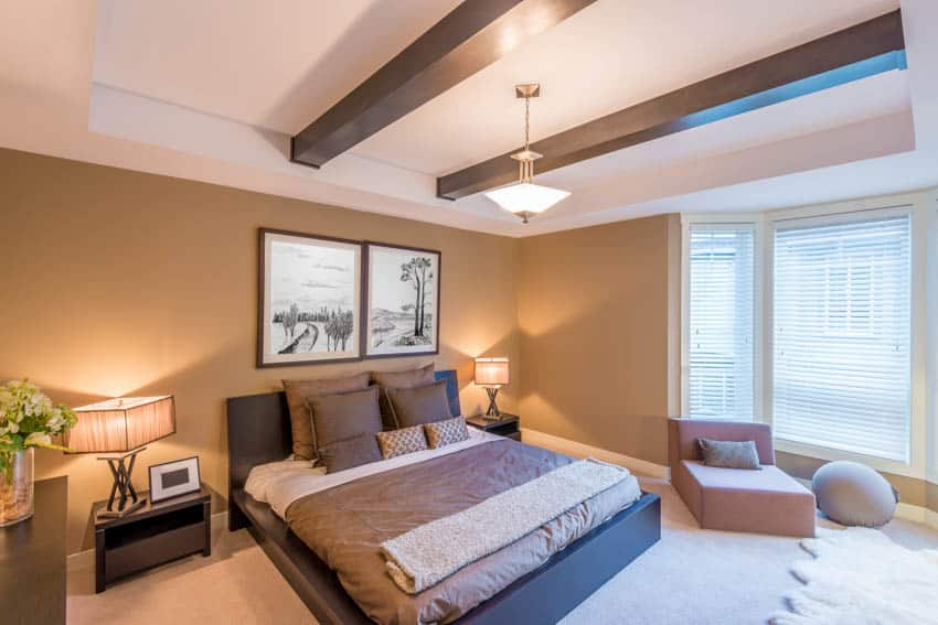 Bedroom with gold accents coffered ceiling window lamps and sofa chair
