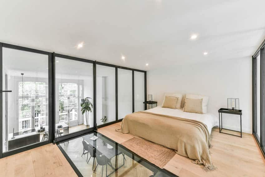Bedroom with gold blanket pillows wood floor white wall ceiling lights glass windows