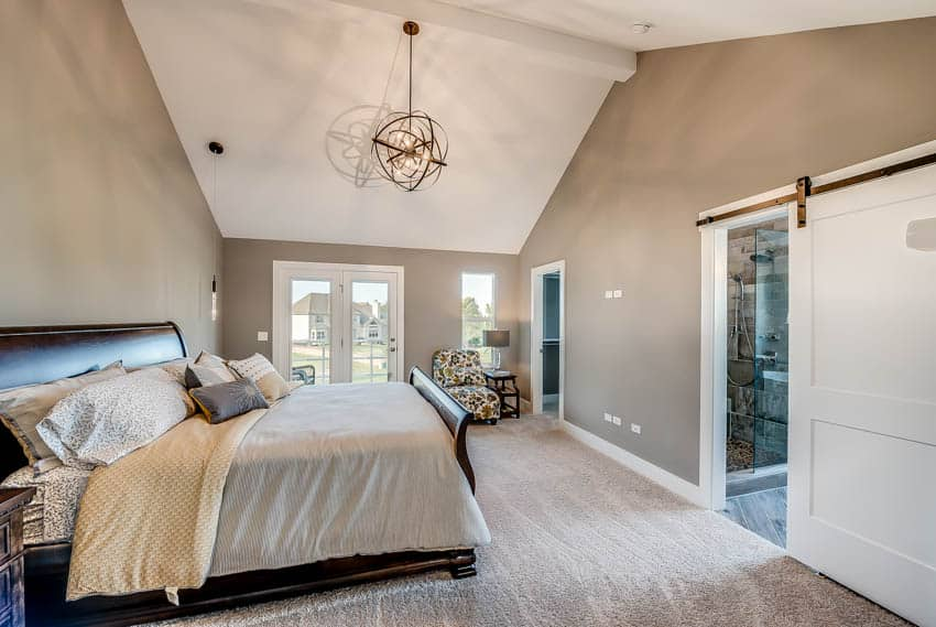 Bedroom with gold hanging light blankets and barn door