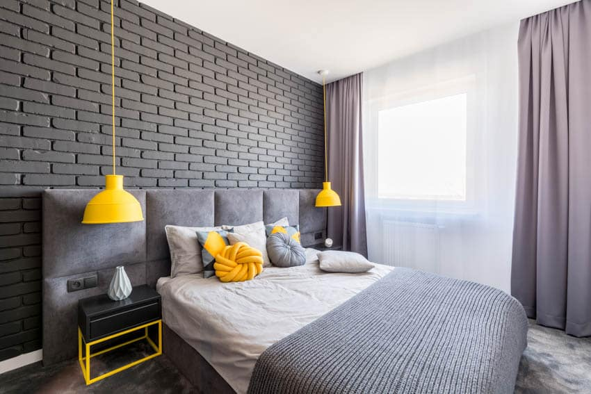 Bedroom with gray brick pattern wall curtains and yellow hanging light