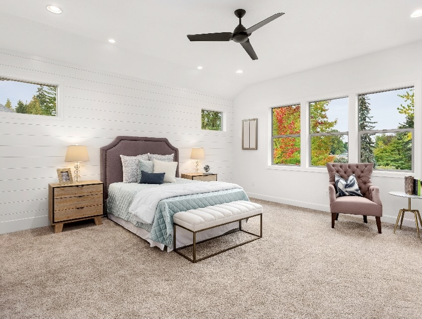 bedroom with large windows ceiling fan carpet and white wall