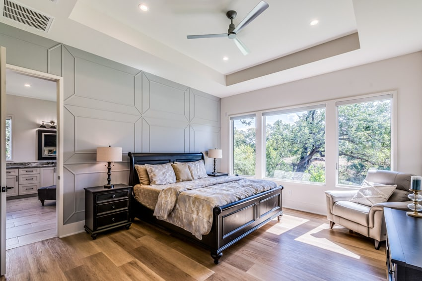 Bedroom with wooden floor large window and furniture