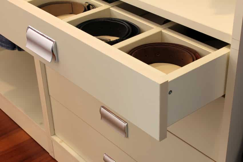 Belts coiled inside white drawer